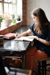 Author writing on paper to break through writer's block